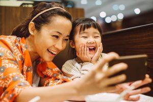 Mom & toddler taking selfies in restaurant
